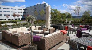 Bilde av uteområde til hotellet fyllt med sofaer og bord, med deler av hotellet i bakgrunnen